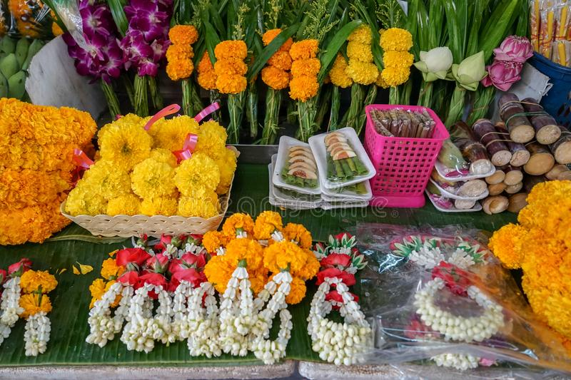 Varieties of Thai style temple offering including garlands made of white jasmine, crown flower, red rose and yellow marigold stock photo