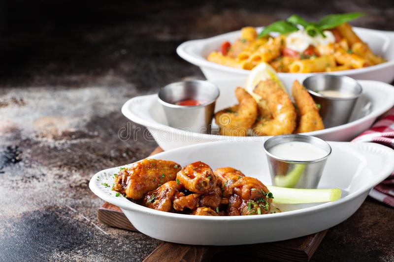 Variety of appetizers with fried shrimp and wings. Variety of appetizers with fried shrimp and hot wings royalty free stock image