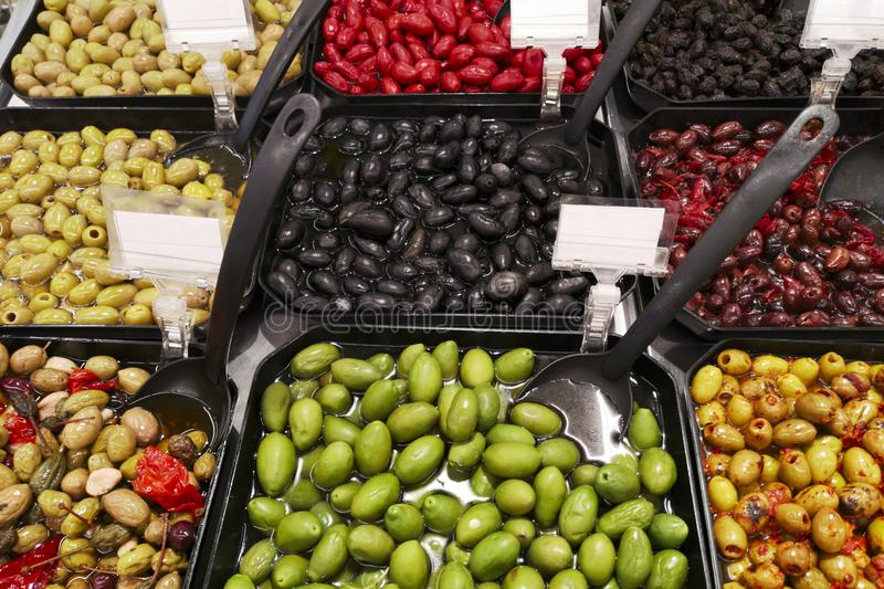 Variety assortment diverse of healthy tasty green and black olives in black plastic bowls for sale on open street city market royalty free stock photo