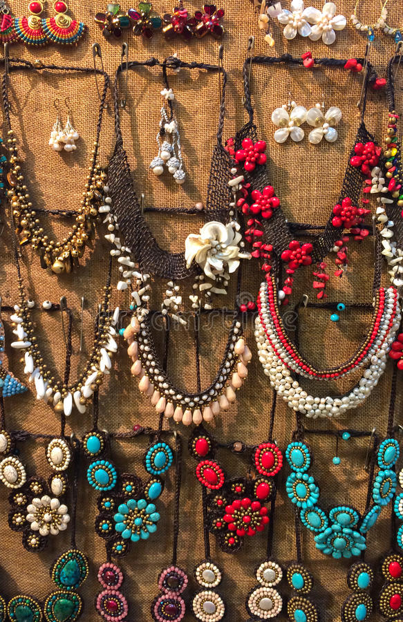 Variety of Beautiful Shiny Color Stone Necklaces Hanging on The Wall for Sale royalty free stock photos