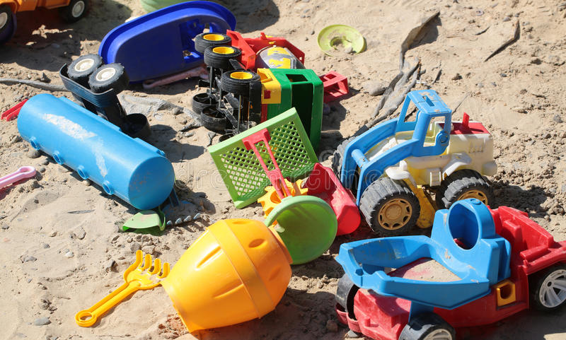 Variety of boyish cars toys. Variety of multicolored yellow red blue green plastic childish cars lorries transport toys summertime outdoor boyish fun game in royalty free stock photography