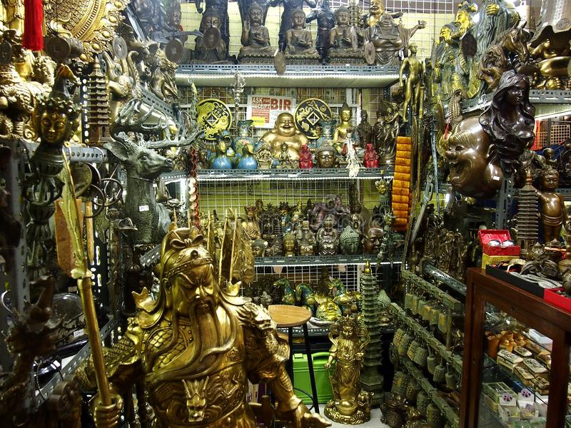 A variety of brass Asian figurines for sale. SAN JUAN CITY, PHILIPPINES - AUGUST 7, 2016: A variety of brass Asian figurines for sale at a shop inside the royalty free stock photos