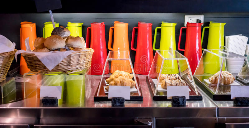 Variety bread and baked goods against colorful beverage container background. In modern bakery shop. Selective focus stock photo
