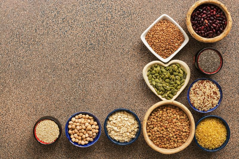 A variety of cereals, legumes, seeds on a brown stone background. Superfood set. View from above royalty free stock images