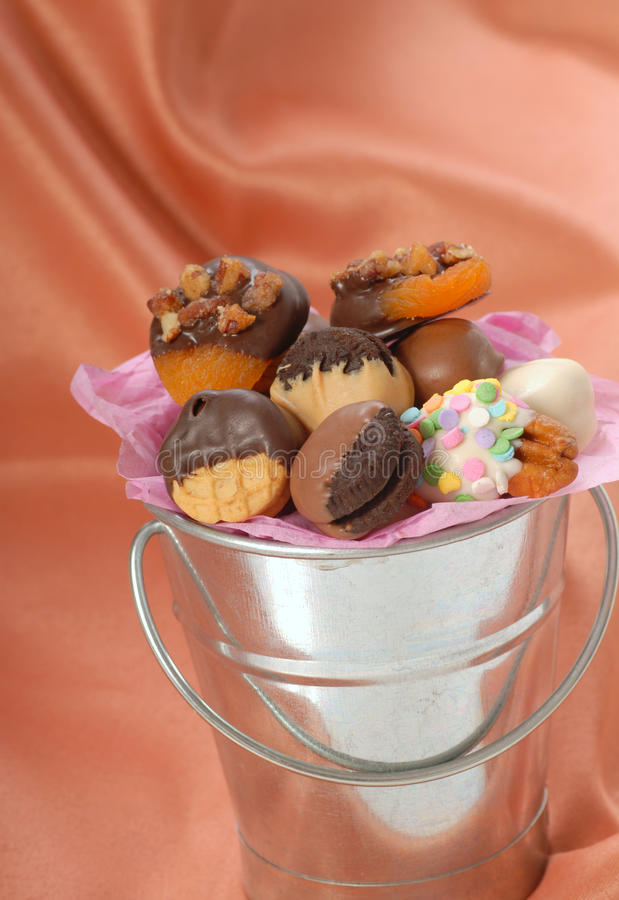 Variety of chocolate covered confections. Silver bucket containing a variety of delicious chocolate covered candies and nuts stock image