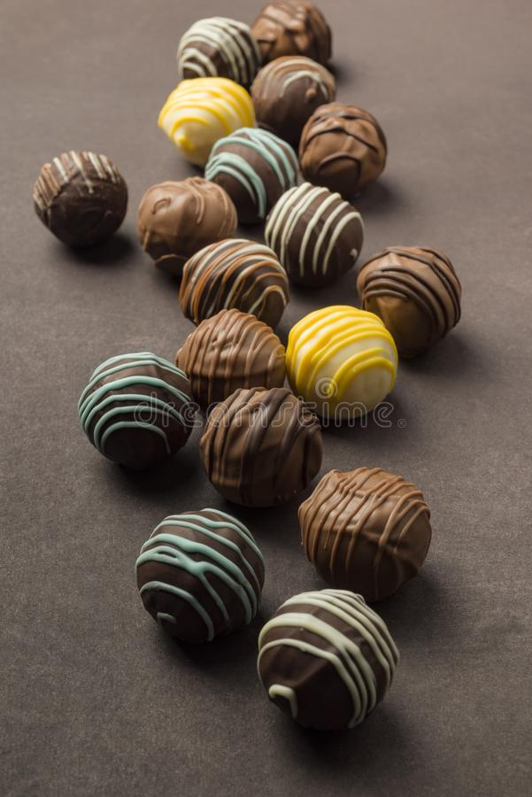 Variety of chocolates. Chocolates praline variety on brown background stock images