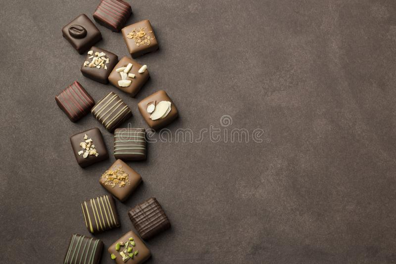 Variety of chocolates. Chocolates praline variety on brown background with copyspace stock photo