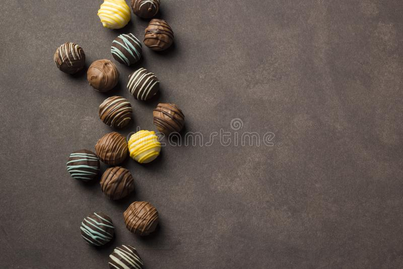 Variety of chocolates. Chocolates praline variety on brown background with copyspace royalty free stock photography