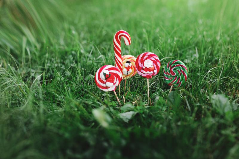 A variety of Christmas candies on the background of green grass. Colored sweets from Santa, snowman and Christmas sock royalty free stock images