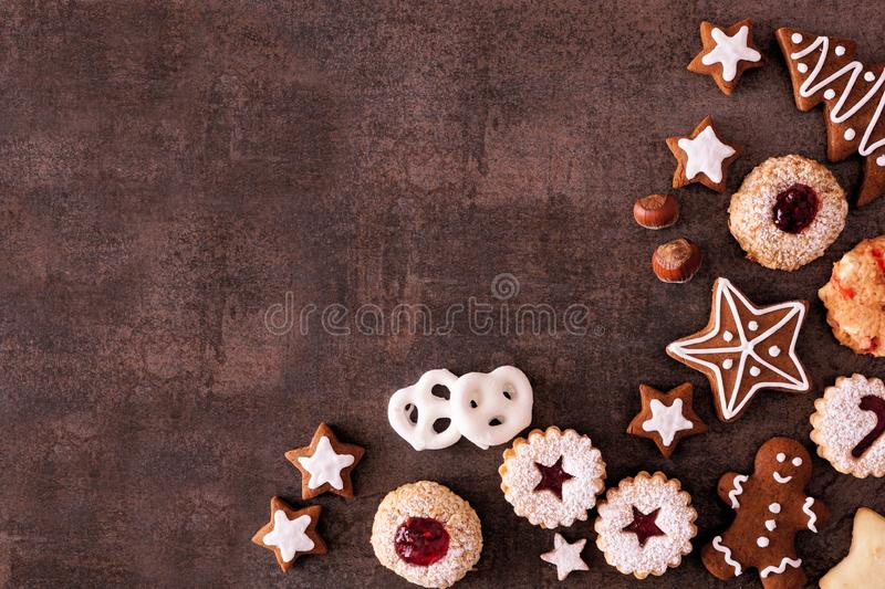 Variety of Christmas cookies and baked sweets, overhead view corner border over a dark stone background. Variety of Christmas cookies and sweets. Overhead view stock image