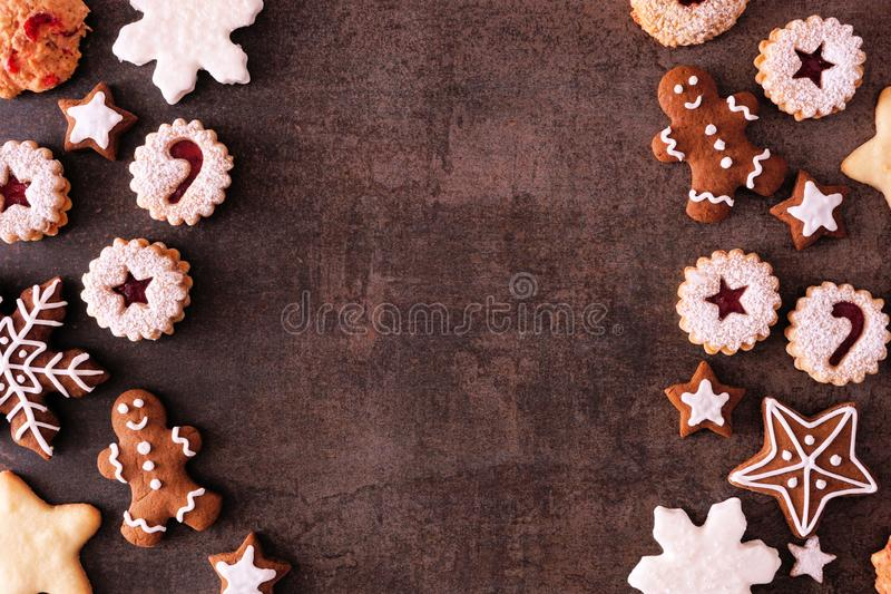 Variety of Christmas cookies and baked sweets, top view double side border over a dark stone background. Variety of Christmas cookies and sweets. Top view double stock photography