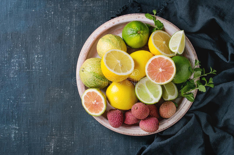 Variety of citrus fruits with tiger lemon. Variety of whole and sliced citrus fruits pink tiger lemon, lemon, lime, mint and exotic lichee on plate with textile stock photos