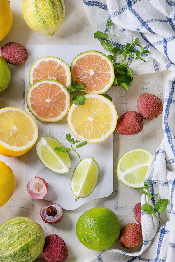 Variety of citrus fruits with tiger lemon. Variety of whole and sliced citrus fruits pink tiger lemon, lemon, lime, mint and exotic lichee on white chopping royalty free stock image