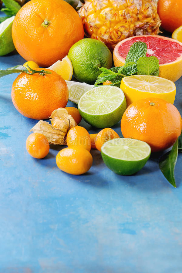 Variety of citrus fruits. Variety of whole and sliced citrus fruits pineapple, grapefruit, lemon, lime, kumquat, clementine and physalis with mint over blue stock photos