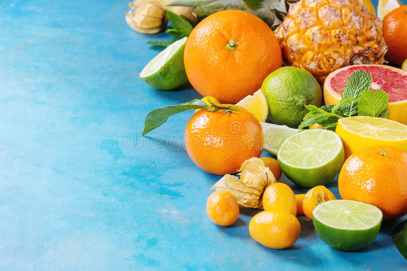 Variety of citrus fruits. Variety of whole and sliced citrus fruits pineapple, grapefruit, lemon, lime, kumquat, clementine and physalis with mint over blue stock photography