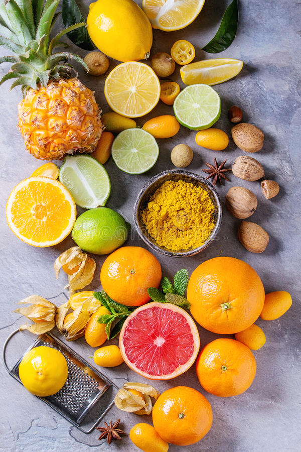 Variety of citrus fruits. Variety of whole and sliced citrus fruits pineapple, grapefruit, lemon, lime, kumquat, clementine and physalis with mint and yellow stock photos