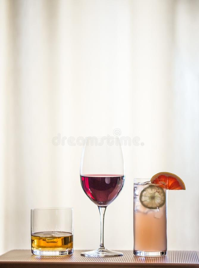 Variety of cocktails in vertical format. Whiskey on the rocks, glass of red wine and a grapefruit vodka spritzer in vertical format stock image