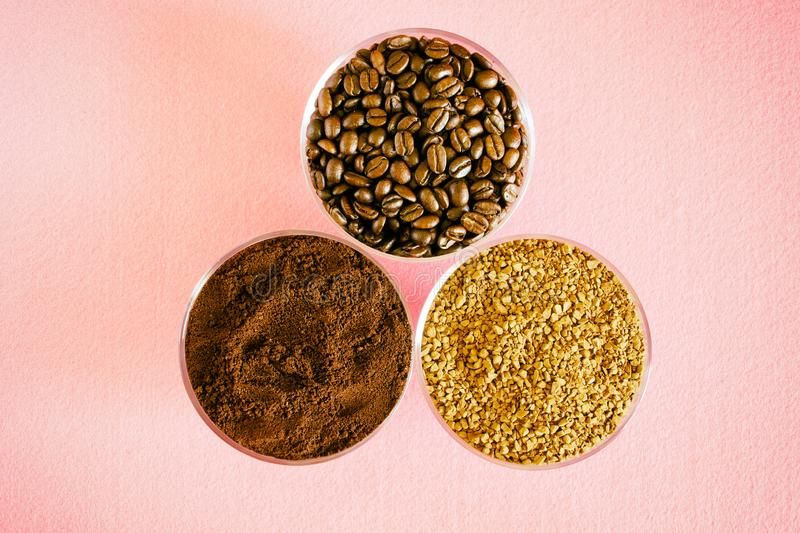 Variety of coffee - three types in one picture: roasted beans, soluble granulated and ground. In round glass bowls on a pink royalty free stock photography