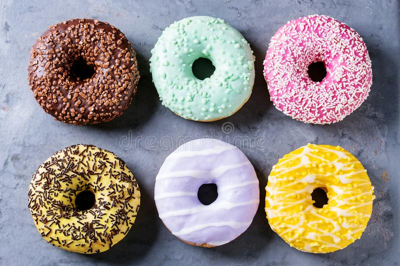 Colorful glazed donuts. Variety of colorful glazed donuts over gray metal texture background. Top view royalty free stock images