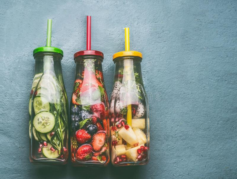 Variety of colorful infused water in bottles with fruits berries, cucumber, herbs and drink straws on gray background, top view. royalty free stock images
