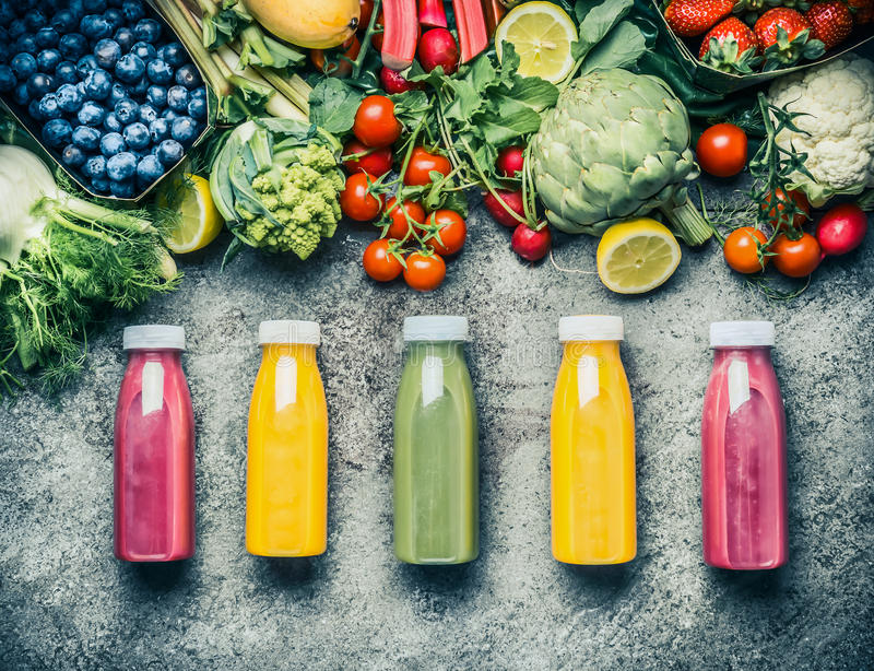 Variety of colorful Smoothies or juices bottles beverages drinks with various fresh ingredients: fruits ,berries and vegetables royalty free stock image
