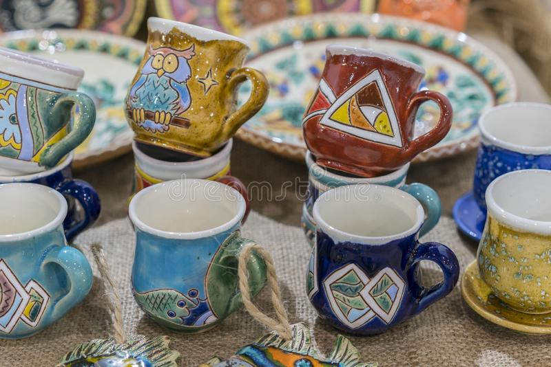 Variety of Colorfully Painted Ceramic Pots in an Outdoor Shopping Market. pottery in the shop window. Clay cups and plates.  royalty free stock images
