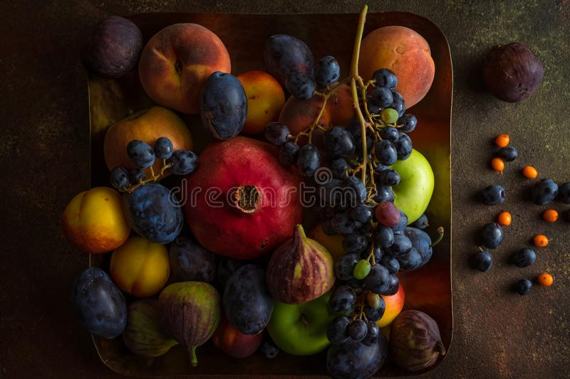 Variety of colourful fruits: pomegranate, grapes, peaches, plums, apples, figs on square platter stock photo