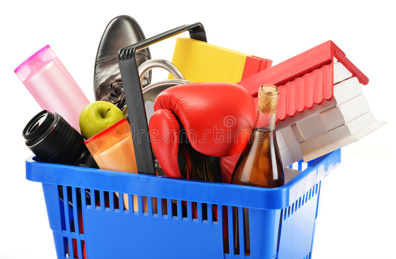 Variety of consumer products in plastic shopping basket isolated. On white royalty free stock photography