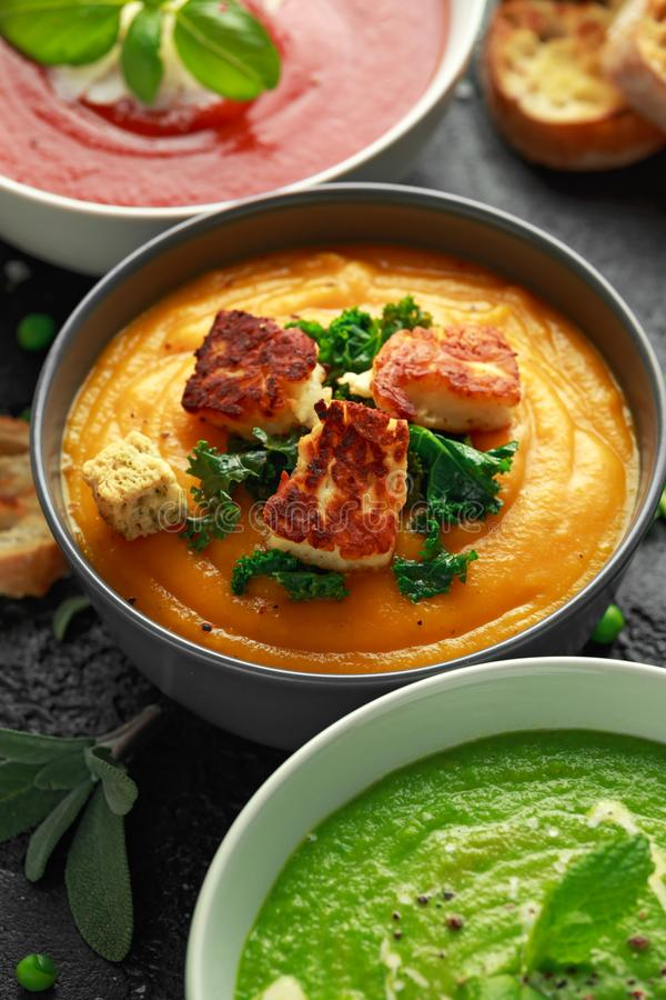 Variety of cream soup bowls: sweet pea and mint, tomato and basil and butternut squash with steamed kale and fried halluomi.  stock photo