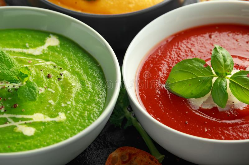 Variety of cream soup bowls: sweet pea and mint, tomato and basil and butternut squash with steamed kale and fried. Halluomi stock photos