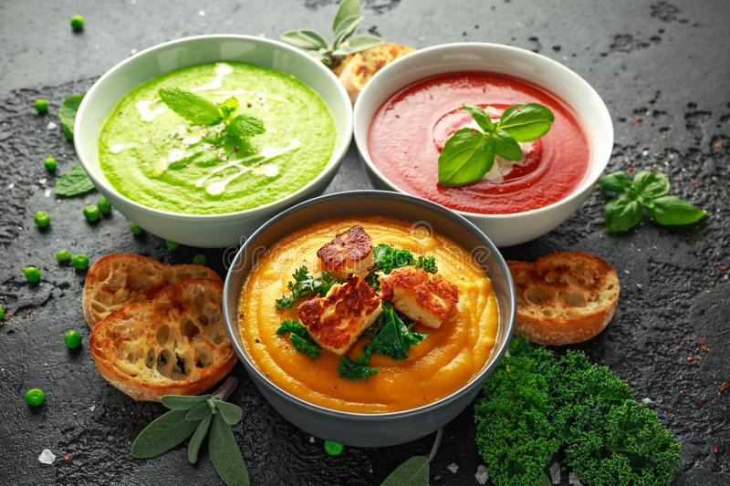 Variety of cream soup bowls: sweet pea and mint, tomato and basil and butternut squash with steamed kale and fried. Halluomi royalty free stock photos