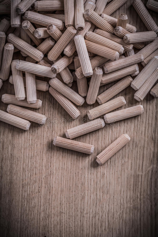 Variety of cylinder wooden dowel pins on wood board construction royalty free stock photos