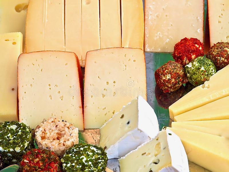 Variety of delicious cheese on a party plate. Gourmet variety of cheese, gouda, cheddar, pepper, cheese balls on a party plate royalty free stock photography