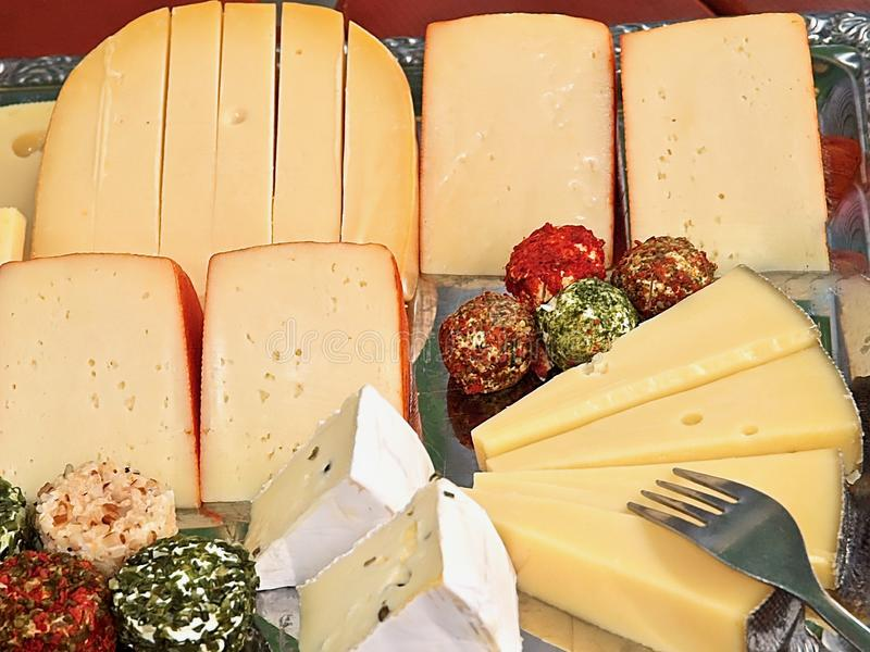 Variety of delicious cheese on a party plate. Gourmet variety of cheese, gouda, cheddar, pepper, cheese balls on a party plate stock image