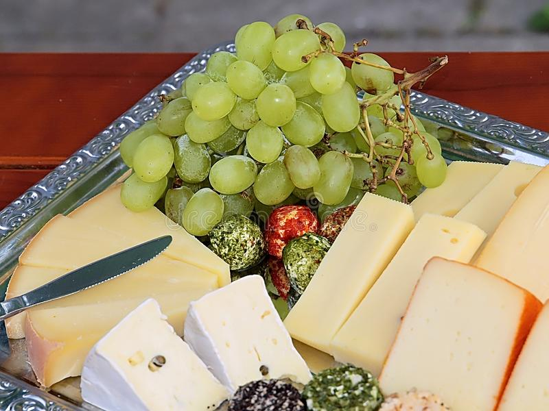 Variety of delicious cheese on a party plate. Gourmet variety of cheese, gouda, cheddar, pepper, cheese balls on a party plate stock photo
