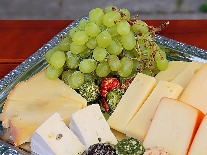 Variety of delicious cheese on a party plate. Gourmet variety of cheese, gouda, cheddar, pepper, cheese balls on a party plate royalty free stock photo