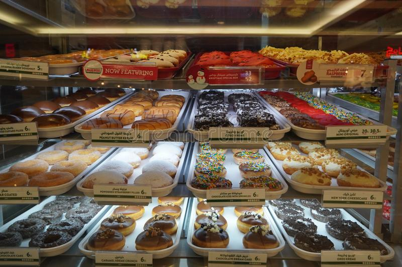 Variety of delicious donut in showcase on display at bakery cake shop Krispy Kreme. Various donuts type on shelf in Bakery shop. stock photo