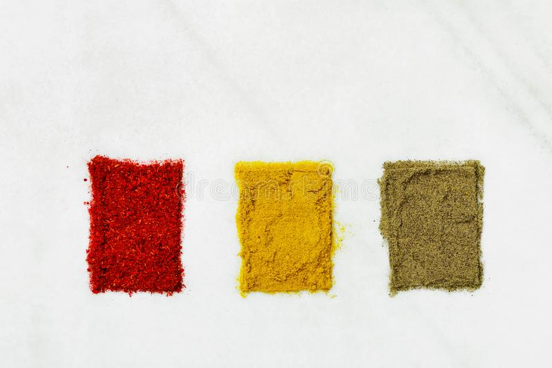 Variety of different ground spices in powder peppers paprika turmeric laid out in color sample boxes on white marble stone royalty free stock photography