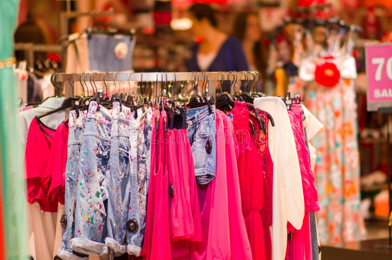 Variety of dresses and shirts on stand in mall. Variety of dresses and shirts on stand in shop stock photo