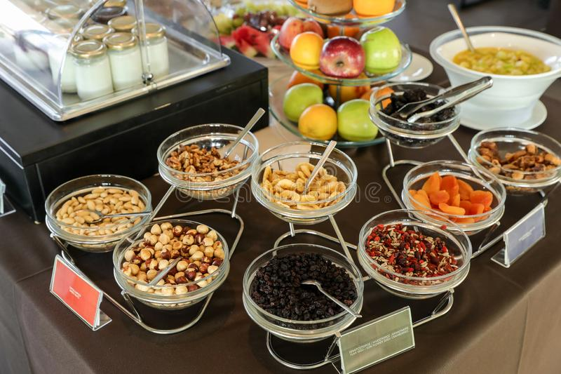Variety of dried nuts and berries for healthy breakfast buffet table as well some fruits and yoghurts in greek hotel. During summer vacation. Horizontal royalty free stock photo