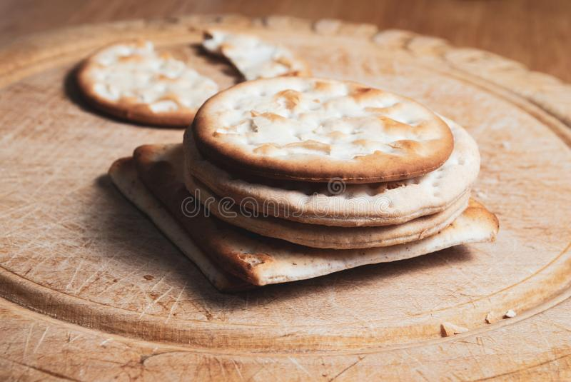 Crackers Stacked on Vintage Bread Board royalty free stock image