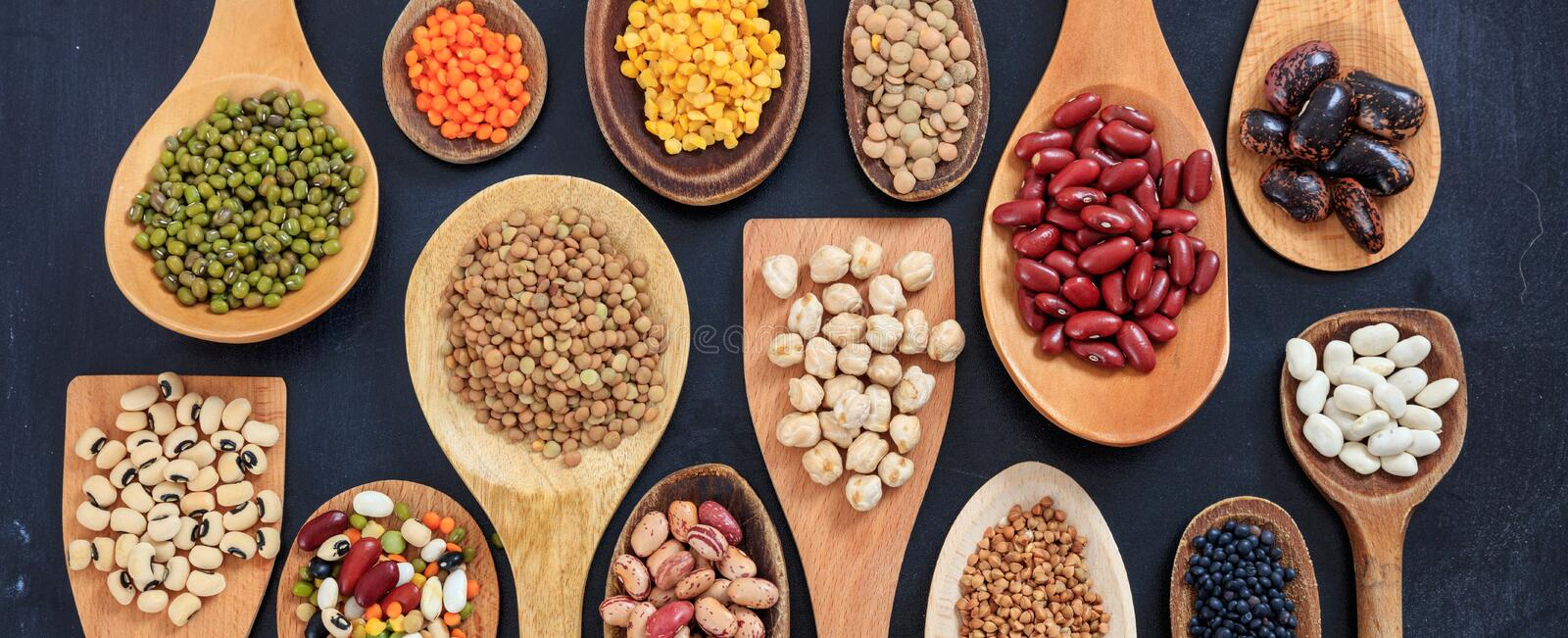 Variety of dry uncooked legumes on wooden spoons, banner royalty free stock photo