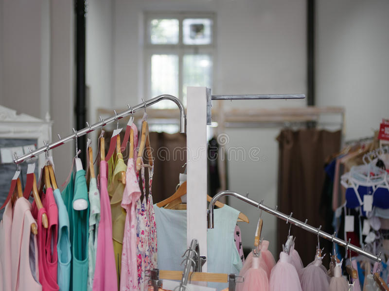Variety of female`s clothes hanging on racks in a luxury boutique. Shopping sale theme. Consumerism concept. stock photos