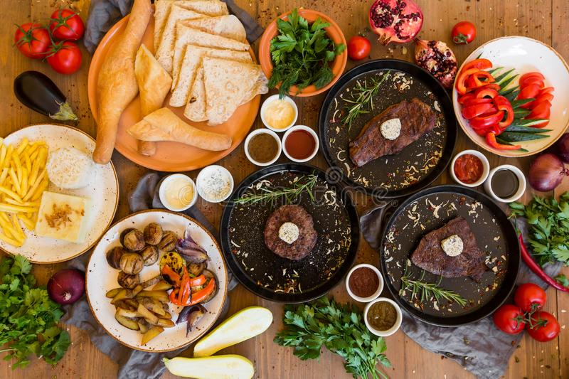 Variety of food grilled on wooden table, top view. Outdoors food Concept stock photos