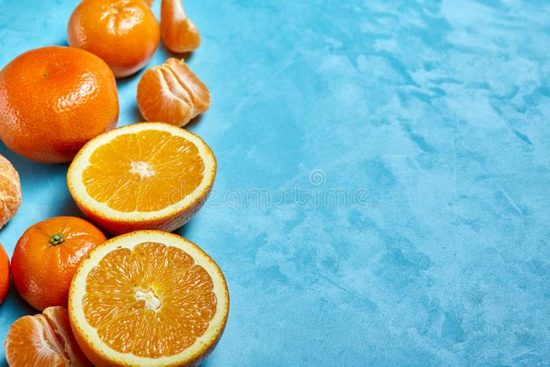 Variety of fresh citrus fruits for making juice or smoothie over blue textured background, top view, selective focus. royalty free stock images