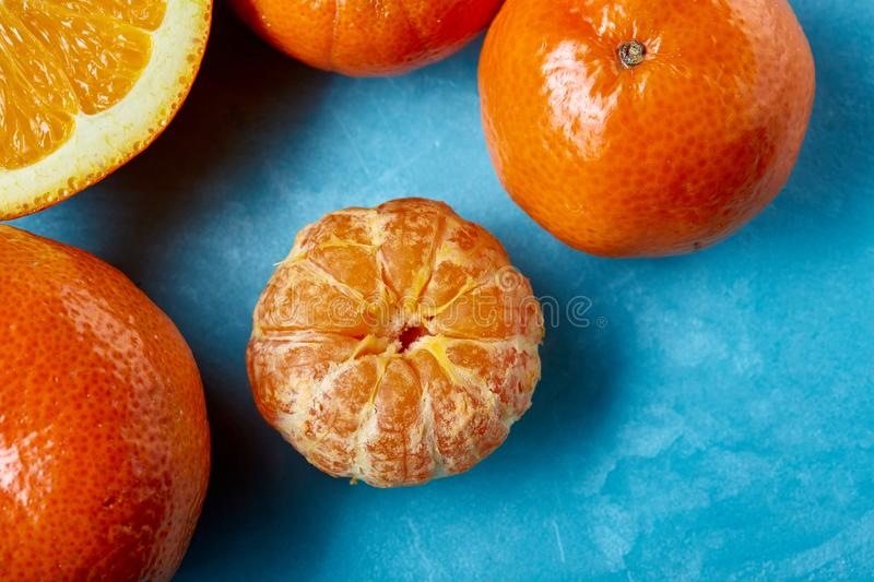 Variety of fresh citrus fruits for making juice or smoothie over blue textured background, top view, selective focus. royalty free stock photo