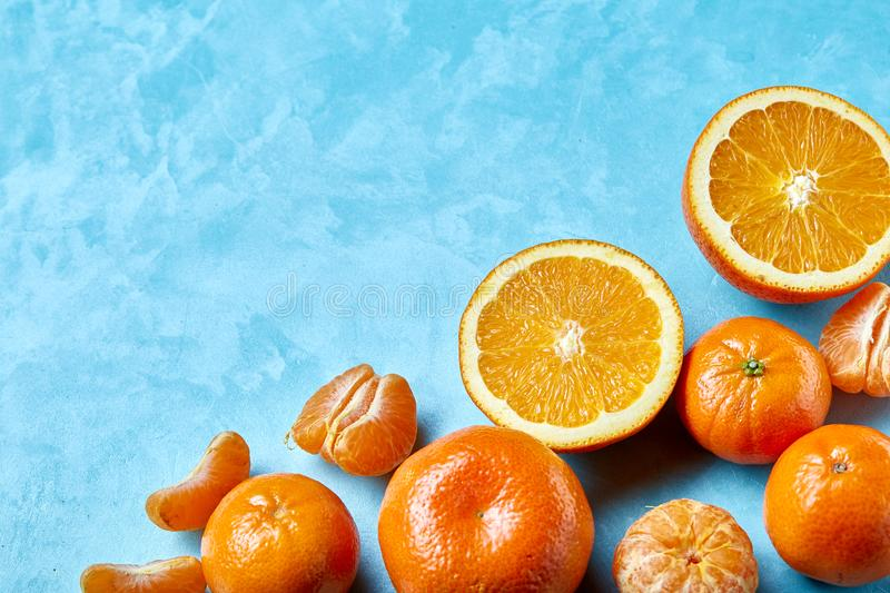 Variety of fresh citrus fruits for making juice or smoothie over blue textured background, top view, selective focus. stock photography