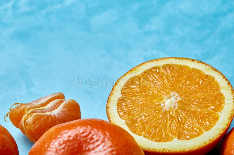Variety of fresh citrus fruits for making juice or smoothie over blue textured background, top view, selective focus. royalty free stock photos