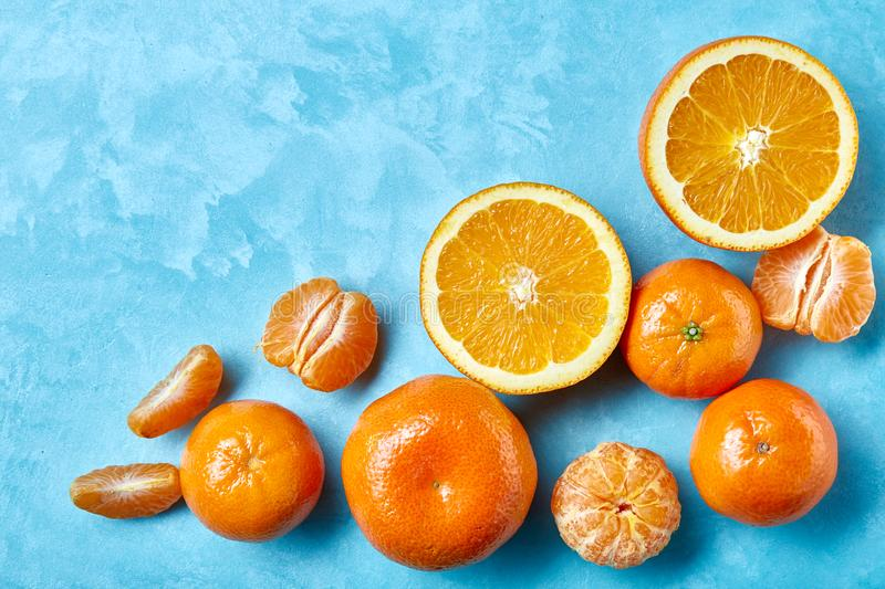 Variety of fresh citrus fruits for making juice or smoothie over blue textured background, top view, selective focus. stock photo