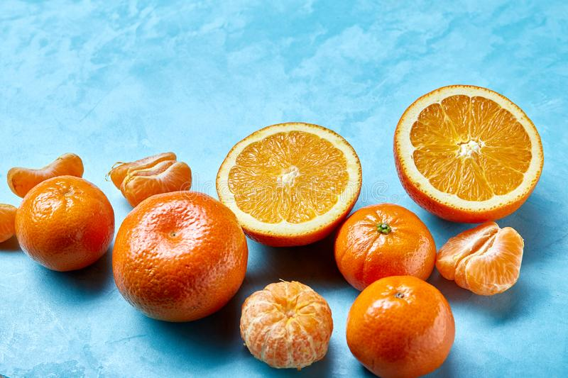 Variety of fresh citrus fruits for making juice or smoothie over blue textured background, top view, selective focus. stock image
